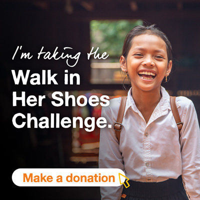 A smiling school girl with a doorway in the background. The text says I'm taking the Walk In Her Shoes challenge. A button says Make a donation.