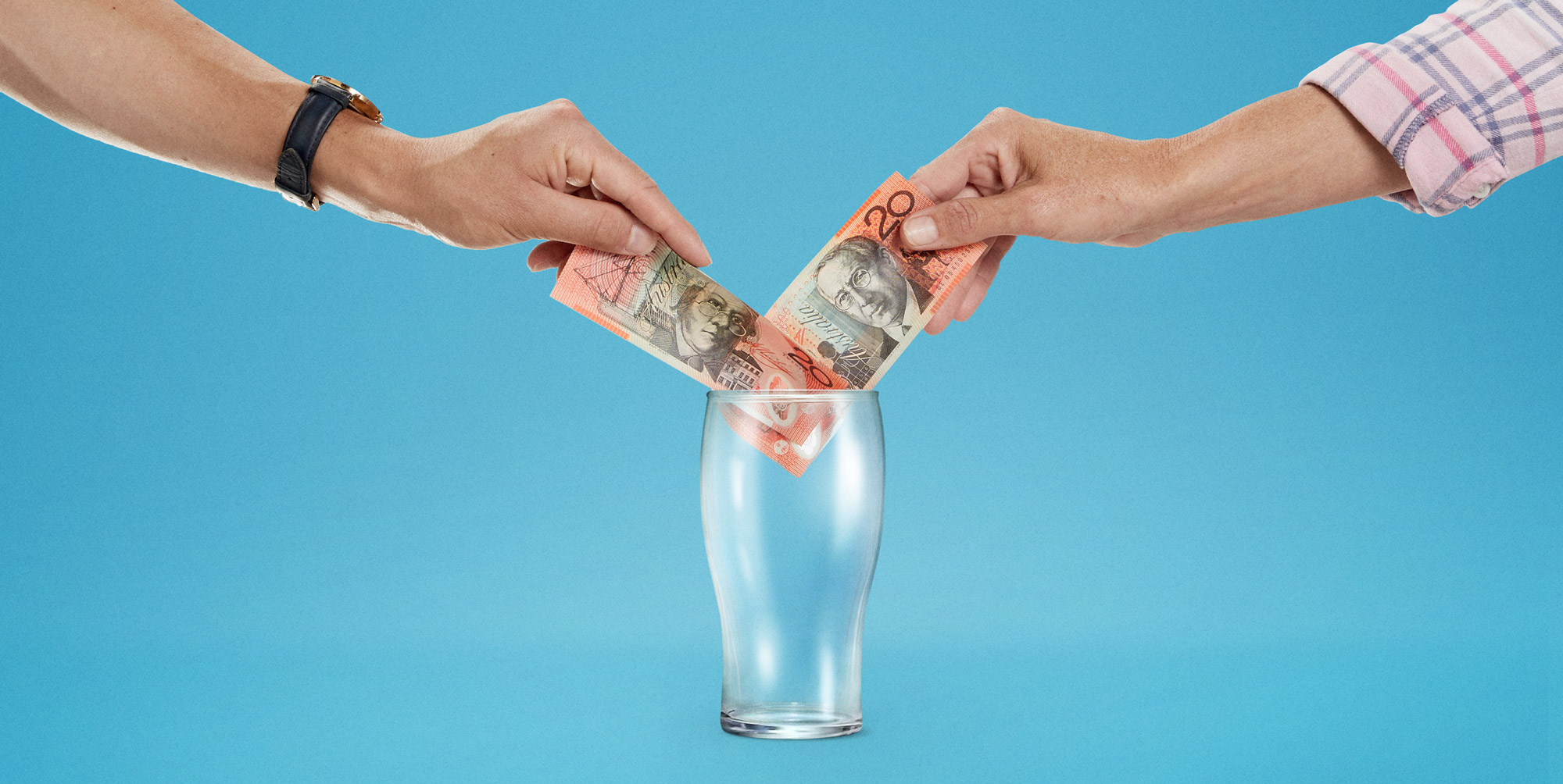 Hands placing money into a beer glass