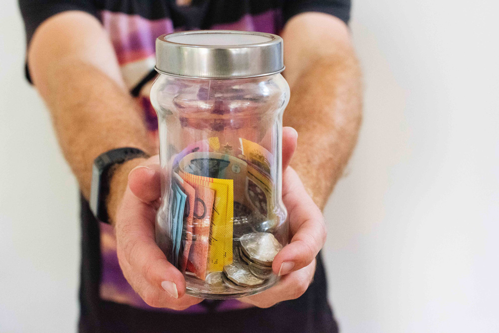 Hands holding jar with money